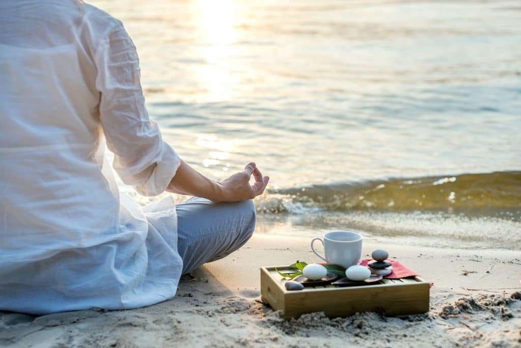 Woman meditating with cup of tea - Focusing on Wellness - The Single Mom Blog